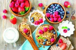 54942662 - healthy breakfast, muesli, raspberries, blueberries, strawberries, crisp bread and yogurt, health and diet concept