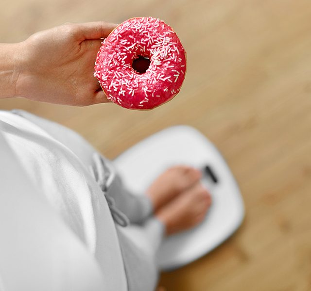 Diet Concept. Woman On Scale Holding Donut. Weight Loss. Dieting