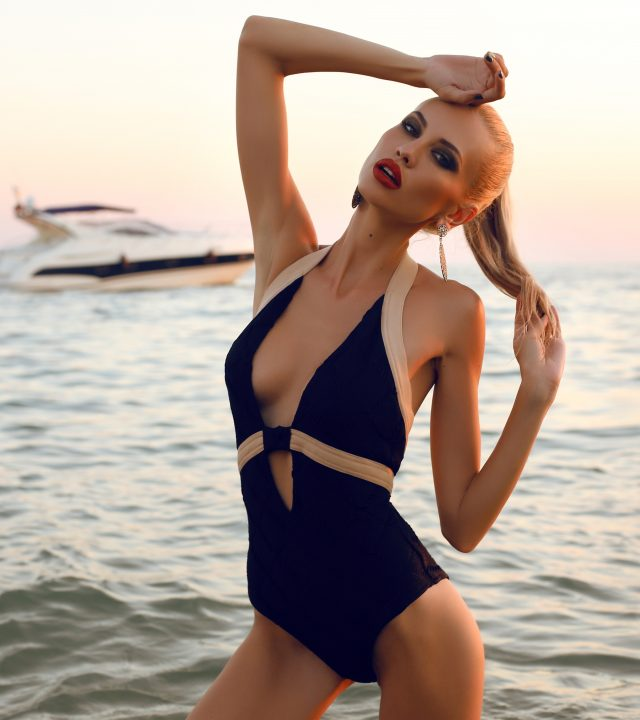 sexy girl with blond hair in swimsuit posing on beach