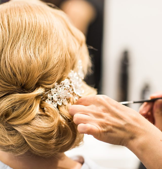 Hair stylist makes the bride before a wedding
