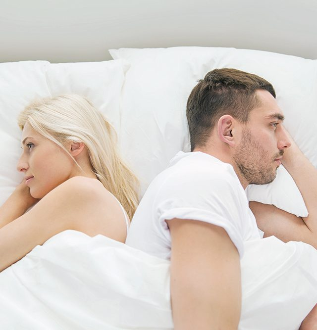 unhappy couple lying in bed at home