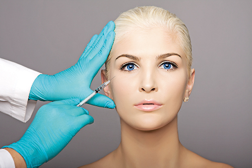 Cosmetic plastic surgeon injecting aesthetics face
