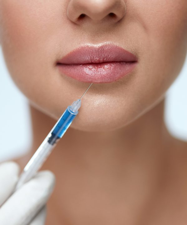 Lip Augmentation. Young Woman Lips Receiving Beauty Injection