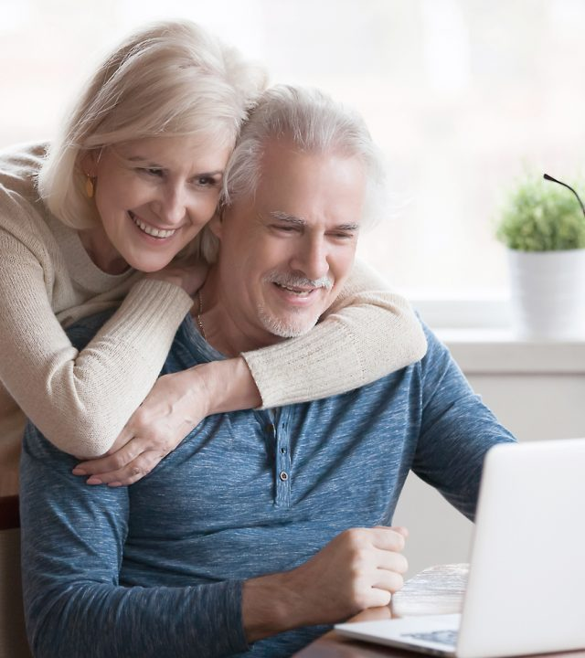 Senior middle aged happy couple embracing using laptop together
