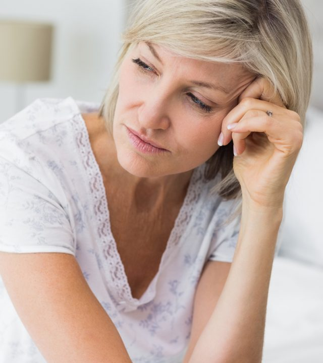 Closeup of a tensed mature woman sitting in bed at home