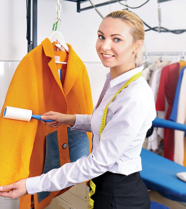 Dry cleaning business concept. Woman working with coat and adhes