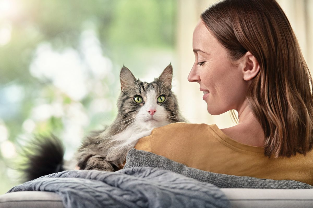 Pro Plan LiveClear Woman sitting on the couch holding her cat